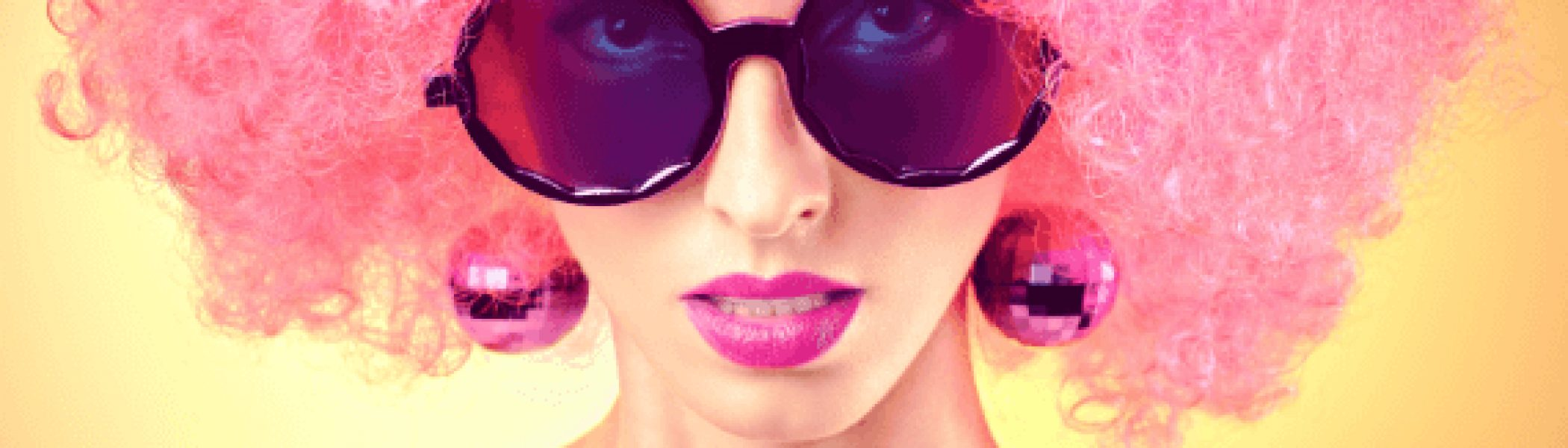 Fashion portrait of sexy nude beauty woman, unusual colourful look. Vivid party lady. Provocative attractive girl in stylish sunglasses with trendy afro hairstyle on yellow. Curly hipster girl face