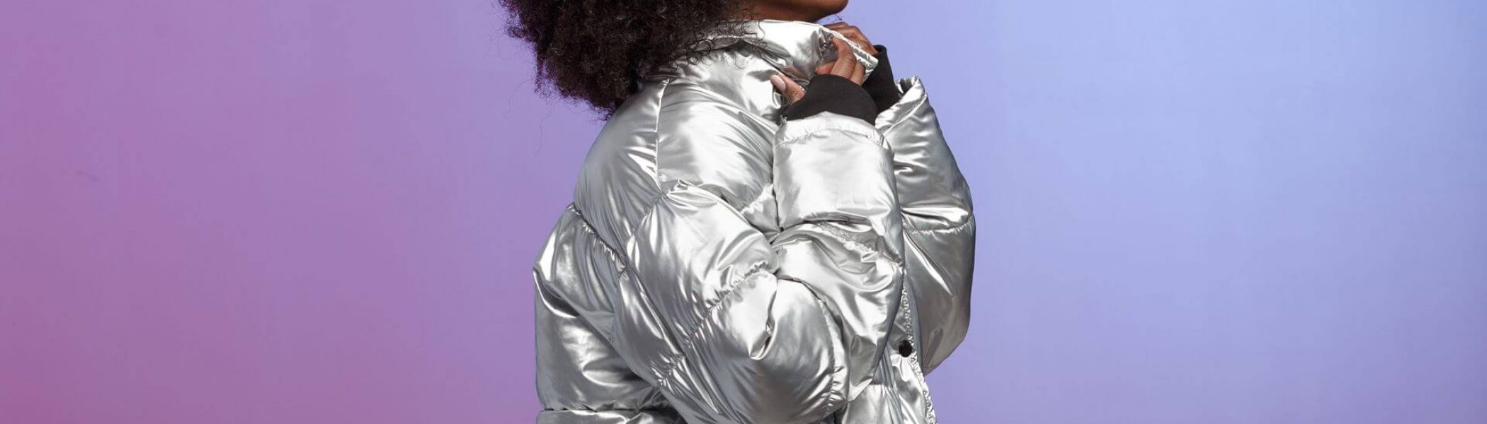 Trendy curly brown-haired girl dressed in a silver-colored jacket uses the virtual reality glasses in the studio on neon background .